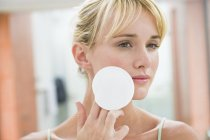 Young woman applying face powder with cotton ball — Stock Photo