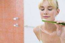 Spiegelbild einer Frau im Spiegel mit Zahnbürste — Stockfoto