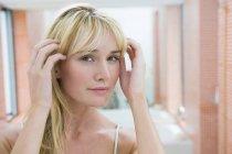 Blonde jeune femme ajuster les cheveux devant le miroir dans la salle de bain — Photo de stock