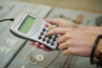 Nahaufnahme des Kunden mit Kreditkartenlesegerät in Boutique — Stockfoto
