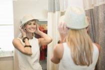 Affascinante donna bionda che prova fedora nella boutique di moda — Foto stock