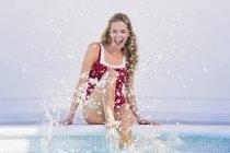 Jovencita alegre sentada junto a la piscina y salpicando agua - foto de stock