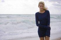 Задумчивая блондинка в платье, стоящая на ветреном пляже — стоковое фото