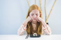 Sad ginger girl sitting at dining table and looking at sushi — Stock Photo