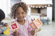 Portrait of little girl showing number blocks — Stock Photo
