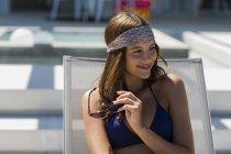 Primo piano di giovane donna sorridente in costume da bagno e bandana che tiene gli occhiali da sole sulla sedia a sdraio — Foto stock