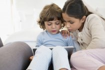 Девушка смотрит на брата с помощью цифрового планшета дома — стоковое фото