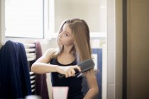 Teenage girl brushing hair with hairbrush in front of mirror at home — Stock Photo