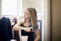 Adolescente escovar o cabelo com escova de cabelo na frente do espelho em casa — Fotografia de Stock