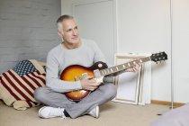 Uomo premuroso che suona la chitarra sul pavimento a casa — Foto stock