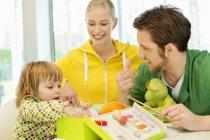 Девушка, сидящая с родителями и изучающая коробку для вязания — стоковое фото
