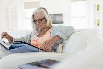 Haute femme assise sur le canapé et la lecture de livre à la maison — Photo de stock