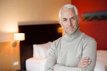 Портрет зрелого мужчины со скрещенными руками в гостиничном номере — стоковое фото