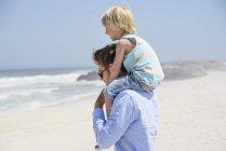 Молодой человек несет сына на плечах на песчаном пляже — стоковое фото