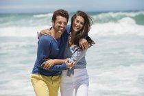 Пара прогулок по пляжу с волнистым морем на заднем плане и смотреть в камеру — стоковое фото