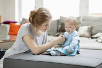 Woman teaching baby daughter with picture book — Stock Photo