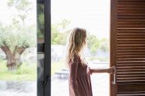 Mulher loira na janela de vidro do terraço — Fotografia de Stock