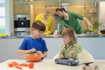 Маленькая девочка с игрушечной машиной смотрит на брата, готовящего на кухне — стоковое фото
