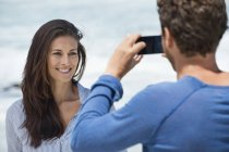 Man taking picture of wife with mobile phone on beach — Stock Photo