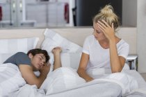 Young woman looking at boyfriend sleeping on bed — Stock Photo