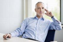 Homme d'affaires confiant s'asseyant dans le bureau et regardant l'appareil-photo — Photo de stock