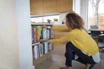 Lockige Frau holt Buch aus Bücherregal in moderner Wohnung — Stockfoto