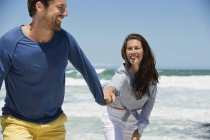 Cheerful couple walking on beach holding hands — Stock Photo