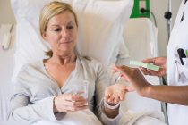Nurse giving pill to patient on hospital bed — Stock Photo