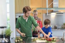 Parents looking at son cutting vegetables in kitchen — Stock Photo