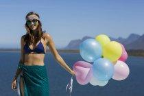 Felice donna elegante che tiene palloncini contro il cielo blu — Foto stock
