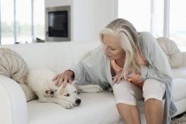 Woman sitting on couch at home and stroking dog — Stock Photo