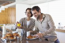 Couple having breakfast at kitchen counter — Stock Photo