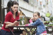 Женщина с маленькой дочерью сидит в кафе и пользуется мобильным телефоном — стоковое фото