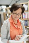 Senior woman reading book in library — Stock Photo