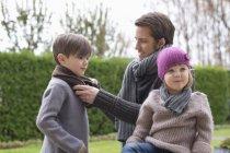 L'uomo indossa vestiti caldi sui bambini all'aperto — Foto stock