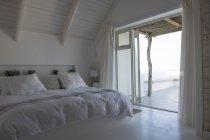 Интерьер уютной белой спальни в современном доме — стоковое фото