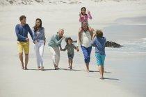 Boy taking photo of family walking on sandy beach — Stock Photo