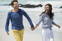 Paar läuft Händchen haltend am Sandstrand — Stockfoto