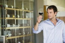 Man looking at red wine in wineglass — Stock Photo