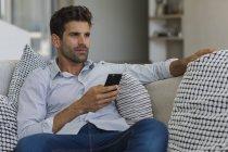 Hombre sentado en el sofá y celebración de smartphone - foto de stock