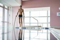 Людина, що стоїть біля басейну і готується плавати — стокове фото