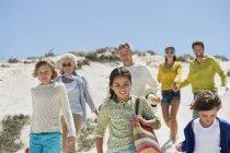 Famille heureuse marchant sur la plage de sable en été — Photo de stock