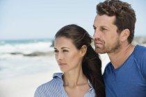 Coppia premurosa guardando lontano sulla spiaggia — Foto stock