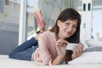 Porträt einer lächelnden Frau, die auf dem Bett liegt und ihr Handy benutzt — Stockfoto