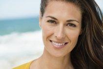 Портрет женщины с каштановыми волосами, улыбаясь на пляже — стоковое фото