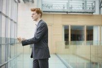 Uomo d'affari guardando attraverso la finestra di vetro nel corridoio ufficio — Foto stock