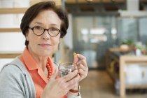 Portrait d'une femme âgée souriante prenant des médicaments — Photo de stock