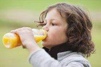 Gros plan du garçon qui boit du jus de bouteille à l'extérieur — Photo de stock