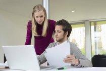 Frau sieht Mann am Laptop arbeiten und Dokumente in der Hand — Stockfoto