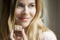Donna in possesso di caramelle al cioccolato e guardando altrove — Foto stock